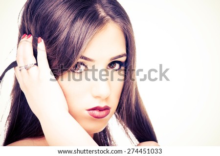 Beautiful young woman posing with her hand in a hair - stock photo