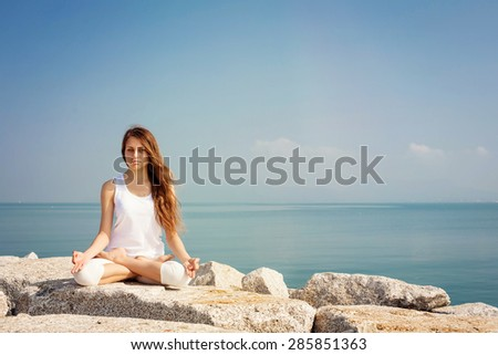 Beautiful young woman practicing yoga and relax in lotus pose at seashore - stock photo