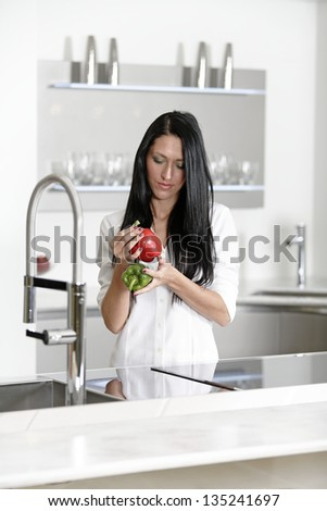 Beautiful young woman preparing food in her modern kitchen at home - stock photo