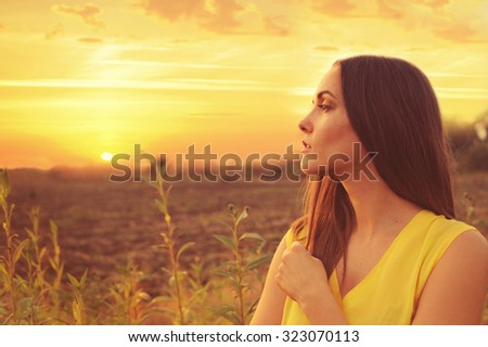 Beautiful young woman profile portrait against sunset autumn field, gazing into infinity. - stock photo