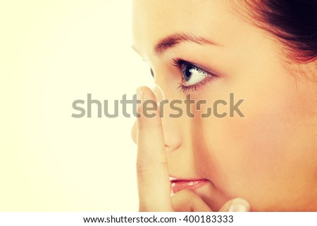 Beautiful young woman putting a contact lens - stock photo