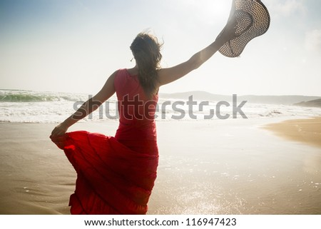 Beautiful young woman raises her hat on a sunny beach - stock photo