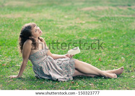 Beautiful young woman reading a book outdoors - stock photo