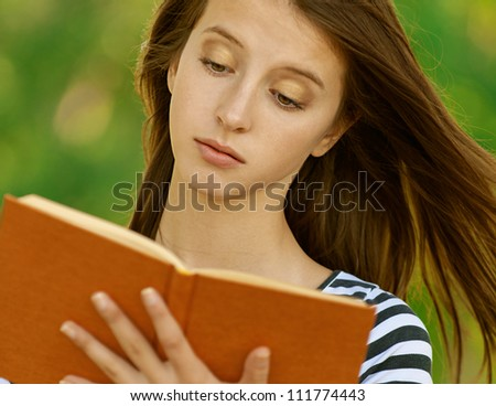 Beautiful young woman reading book, against green of summer park. - stock photo