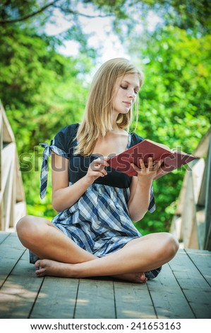 beautiful young woman reading book on green background - stock photo