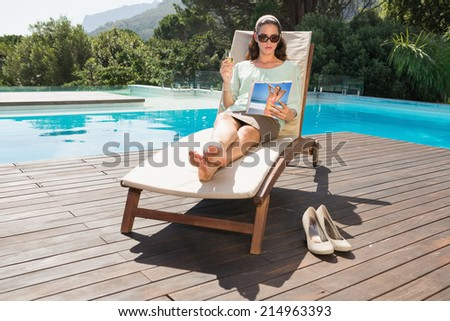 Beautiful young woman reading book on sun lounger by swimming pool - stock photo