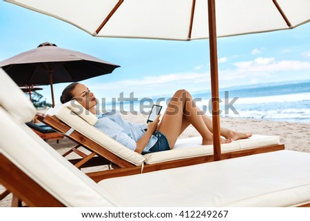 Beautiful Young Woman Reading E-book While Relaxing On Lounger Under Umbrella On Beach On Summer Holidays Vacations. Girl With Electronic Book Lying On Deck Chair Under Tent By Sea In Leisure Time - stock photo