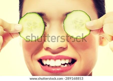 Beautiful young woman receiving facial mask of cucumber. - stock photo