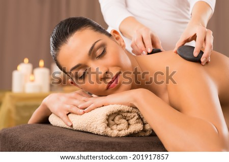 Beautiful Young Woman Receiving Hot Stones Massage At Day Spa - stock photo