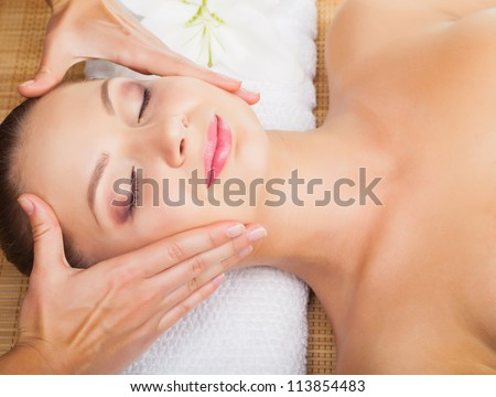 Beautiful young woman receiving massage of head in beauty salon - stock photo