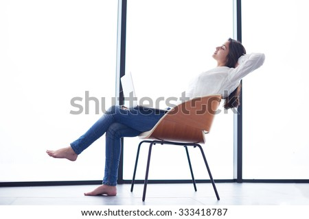 beautiful young woman relax and work on laptop computer modern  home office while listening musin on white headphones - stock photo