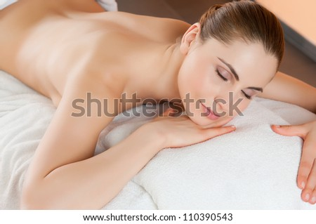 Beautiful young woman relaxing and lying at health spa club - stock photo