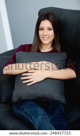 Beautiful young woman relaxing at home on her sofa - stock photo