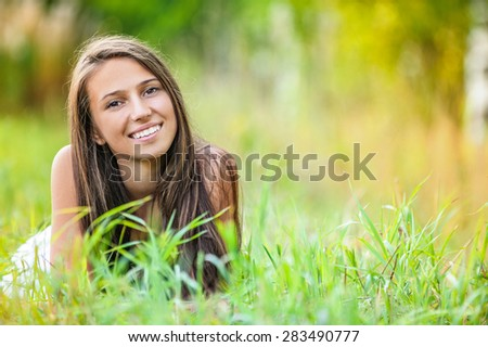 beautiful young woman relaxing grass lying leaning hands person leaned - stock photo