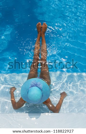 Beautiful young woman relaxing in a swimming pool - stock photo