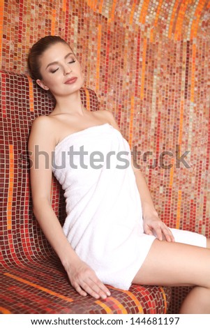 Beautiful young woman relaxing in a Turkish bath at spa. - stock photo