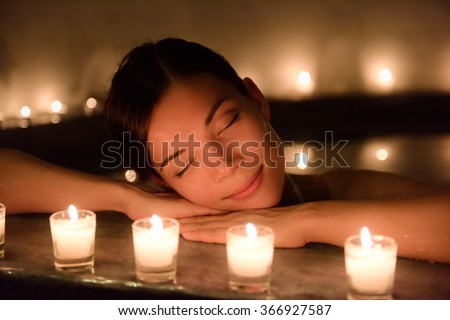 Beautiful young woman relaxing in jacuzzi hot tub at spa. Attractive female tourist is surrounded with lit candles. Smiling woman with eyes closed is pampering herself during vacation. - stock photo