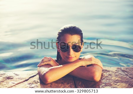 Beautiful young woman relaxing in pool at sunset, Luxury resort fashion lifestyle - stock photo