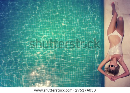 Beautiful young woman relaxing in the swimming pool - stock photo