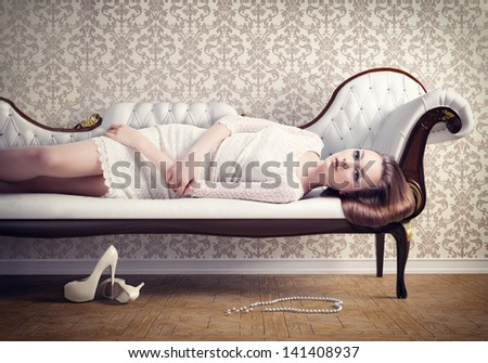 Beautiful young woman relaxing on a vintage sofa - stock photo