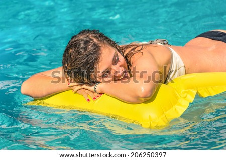 Beautiful young woman relaxing on a yellow inflatable mattress in clear blue water - Summer chilling out with girl in swimming pool at exclusive hotel resort - stock photo