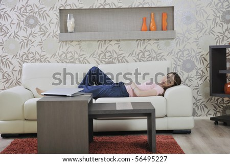 beautiful young woman relaxing on sofa at home - stock photo