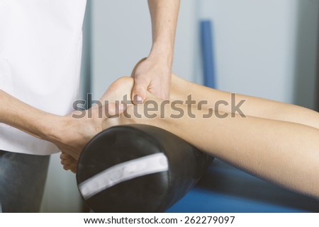 Beautiful young woman relaxing with hand massage at beauty spa - stock photo