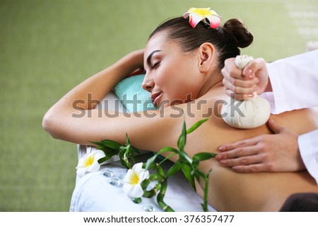 Beautiful young woman relaxing with hand massage at beauty spa, closeup - stock photo