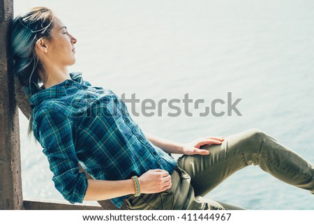 Beautiful young woman resting on coast and enjoying view of sea - stock photo