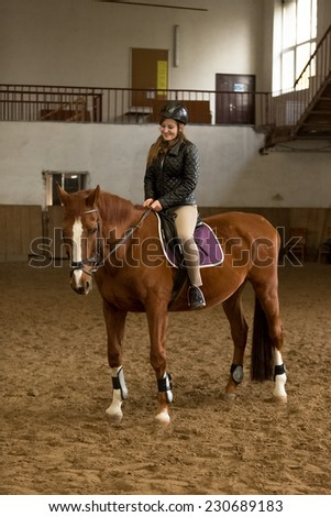 Beautiful young woman riding brown horse in indoor manege - stock photo