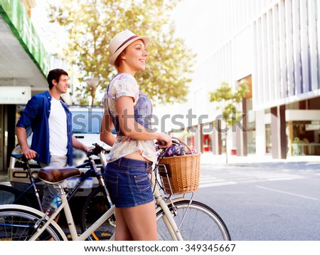 Beautiful young woman riding on bike in city - stock photo