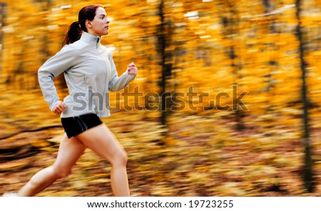 Beautiful young woman running in a fall forest. - stock photo