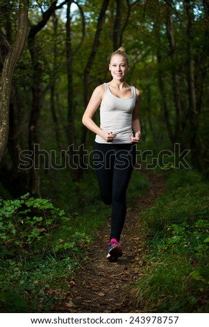 beautiful young woman runs in forest - stock photo