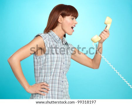 beautiful young woman, screaming on the telephone, on blue background - stock photo