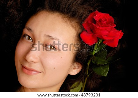 Beautiful young woman serene face with a red rose - stock photo