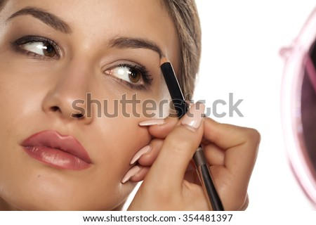 beautiful young woman shaping her eyebrows with a pencil - stock photo