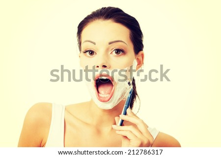 Beautiful young woman shaving her face with a razor - stock photo