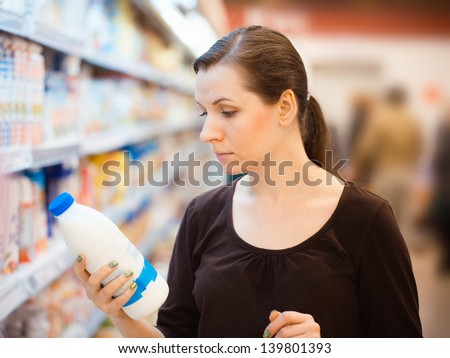 Beautiful young woman shopping for milk in a grocery supermarket - stock photo