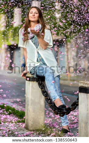 Beautiful Young woman showered pink petals cherry blossoms in the air in spring day - stock photo