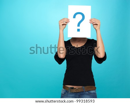 beautiful, young woman showing a question mark on a white piece of paper in front of her head, on blue background - stock photo