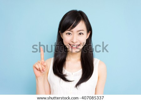 beautiful young woman showing copy space against blue background - stock photo