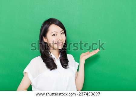 beautiful young woman showing copy space against green background - stock photo