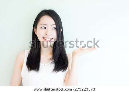 beautiful young woman showing copy space against light green background - stock photo