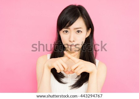 beautiful young woman showing NO gesture against pink background - stock photo