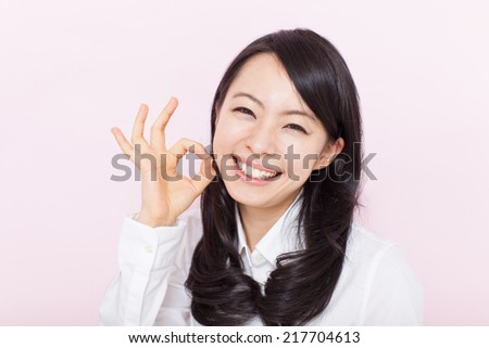 beautiful young woman showing OK gesture against pink background - stock photo