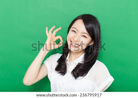 beautiful young woman showing OK sign against green background - stock photo