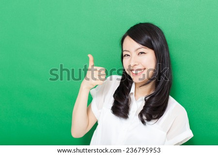 beautiful young woman showing thumbs up gesture against green background - stock photo