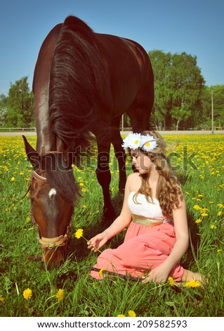 Beautiful young woman sits in the field with a horse - stock photo