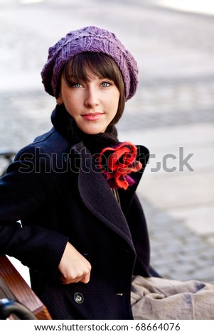 beautiful young woman sitting and looking straight to the camera - stock photo