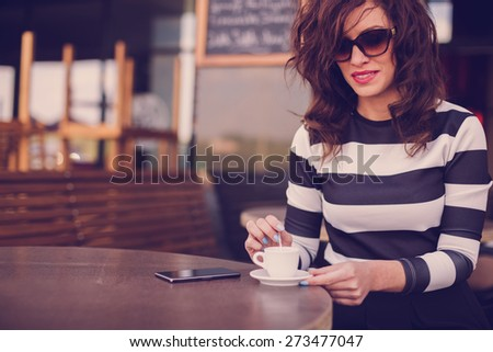 Beautiful young woman sitting in a cafe and mixes coffee with the spoon. On table she has her mobile phone ready to call her friends to join her - stock photo